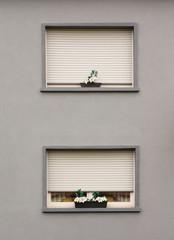 Graue Fassade mit zwei Fenstern und geschlossenen Rollläden