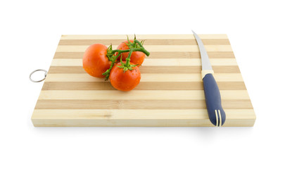 three tomatoes on the green branch on the desk with knife isolat