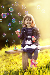 Portrait of a girl sitting on a wooden bench blows bubbles in th