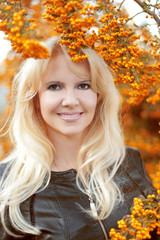 Beautiful smiling blond woman with long hair over autumn yellow
