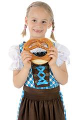 Mädchen in Dirndl zum Oktoberfest hält Laugenbrezel