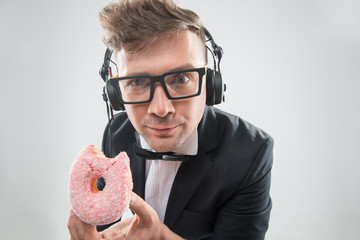 Dj eating donut on working place close-up
