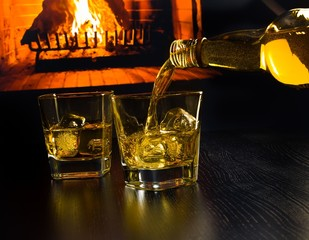 man pouring two glasses of whiskey with ice cubes near fireplace