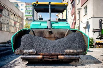 industrial paver laying fresh asphalt and bitumen pavement