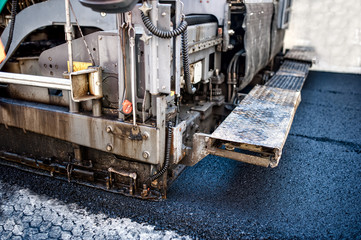 pavement machine laying fresh asphalt or bitumen