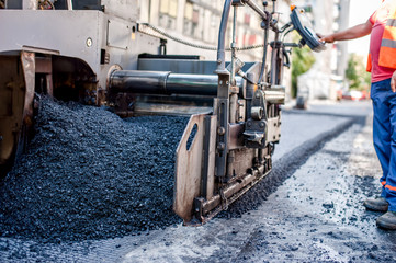 worker or engineer operating an ashphalt paving machine at road