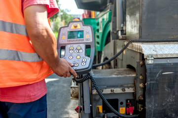 close up of worker hand operating asphalt paver machinery