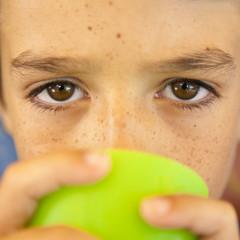 Ojos de niño con pecas bebiendo