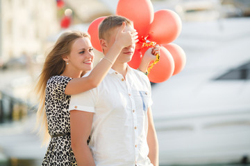 Young couple with colourful balloons in town.