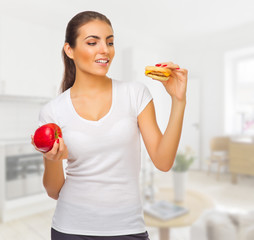 Girl with apple and hamburger at light room