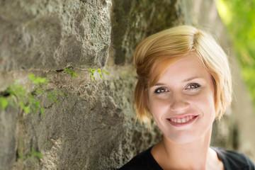 lächelnde junge frau lehnt an steinmauer