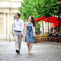 Couple walking in Paris near a street cafe