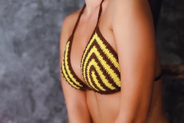 Bosom of model in knitted bikini