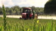 farmer spray agricultural tractor fertilizer on cereal field
