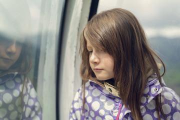 Trauriges kleines Mädchen lehnt an einem Fenster