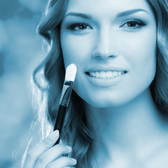 Smiling woman with make up brush