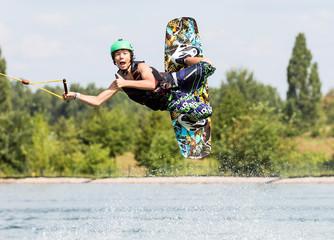 Jugendlicher Wakeboarder zeigt DAUMEN HOCH im Flug