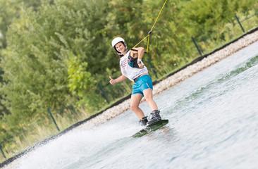 Daumen hoch zeigt junge Frau auf Surfbrett