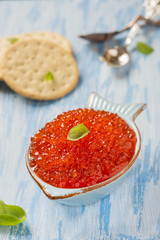 Red caviar in fish-shape bowl with crackers