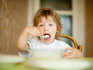 child eats dairy  with spoon