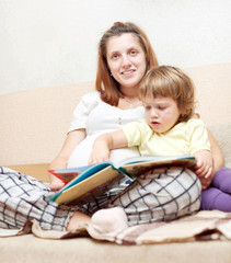 pregnant woman and daughter reads  book