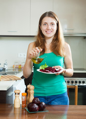 woman in green with boiled beets at home interior