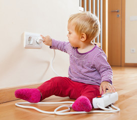 Toddler playing with extension cord and outlet