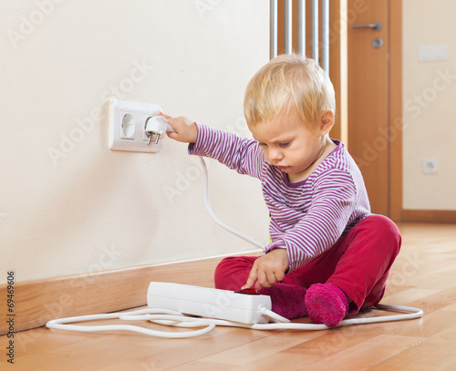 Baby playing with electrical extension - 69469606