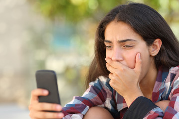 Worried teenager girl looking at her smart phone