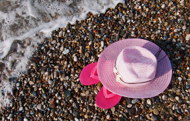 Sun hat and flip flop on the beach.