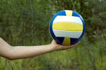 Female hand holds in her palm sports ball for playing volleyball