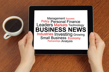 Hands hold tablet PC with tag cloud of business news