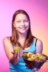 Teen girl holding a colander full of apples