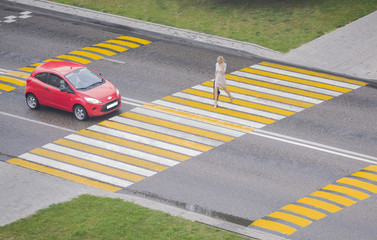 Woman crosses the road on the crosswalk