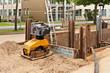 Ein Anbaurüttler für einen Bagger steht neben Verbauplatten