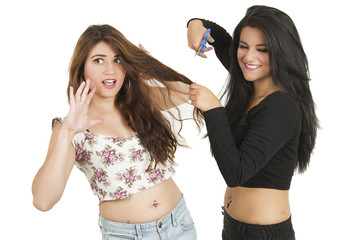 Beautiful young girl trying to cut her worried friend's hair