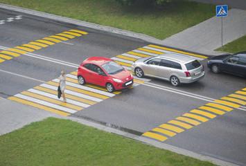 Woman crosses the road on the crosswalk