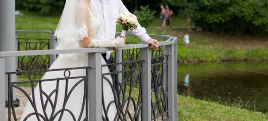 Bride and groom around the fence of the bridge