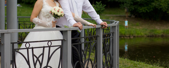 Bride and groom around the fence of the bridge