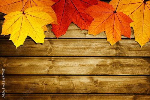 Leinwandbild Motiv wooden background with autumn maple leaves