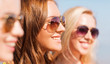close up of smiling young women in sunglasses