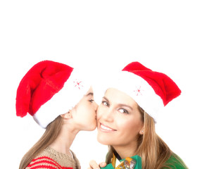 Family, Christmas concept. Adorable child kisses her mother and