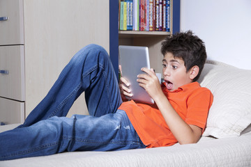 Surprised young boy is sitting with his tablet PC