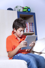Young boy is sitting with his tablet PC