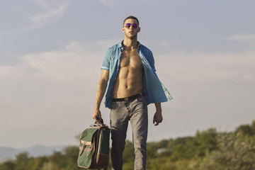 sexy guy in motion with travel bag