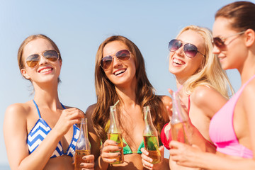 group of smiling young women drinking on beach