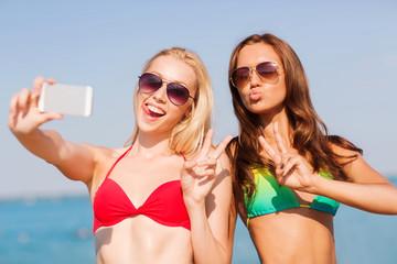 two smiling women making selfie on beach