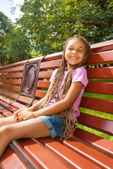 Nice little black girl sitting on e bench in park