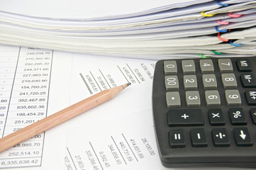 Calculator and pencil on statement with balance sheet