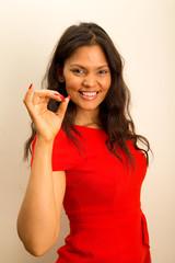 a beautiful latina girl showing an ok symbol.